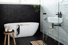 06 large scale black hex tiles cover the floor and go up the wall and contrast the white tiles