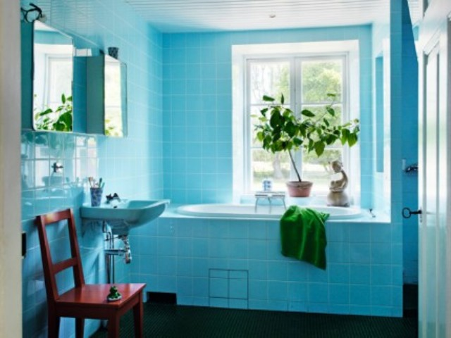 The bathroom is clad with bold blue tiles, there's potted greenery and some green towels, a mid century modern chair is red