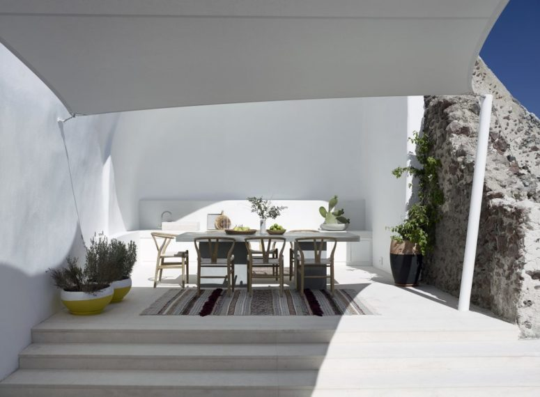 The dining zone is done with a built-in bench, wooden chairs and a concrete dining table