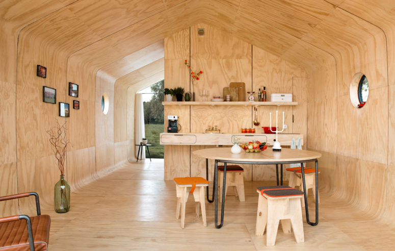 The inside is covered with plywood, there's a small kitchen, a dining space, some shelves