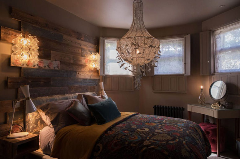 The master bedorom is done with a reclaimed wood headboard, an oversized chandelier and colorful textiles