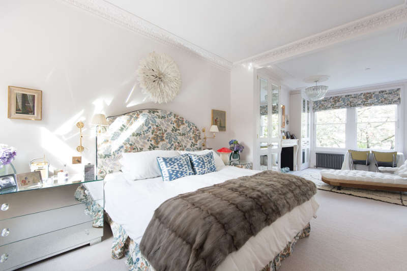 The master bedroom features floral print fabric, which is used for upholsterign the bed, curtains, furniture