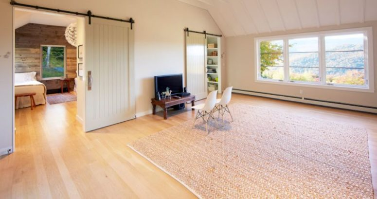 There's a comfortable space for watching TV and just inviting friends, and sliding barn doors make the space cozier yet keep it modern