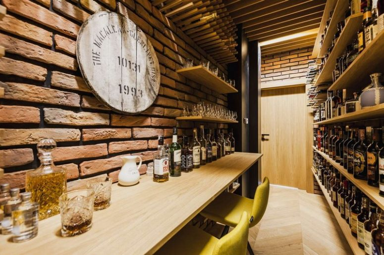 There's a stylish wine cellar with bricks, shelves and colorful chairs for comfortable tasting