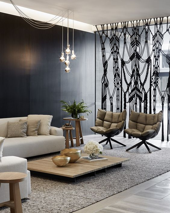 a cool modern space with a black wooden wall, neutral furniture and a black macrame space divider to make it bolder