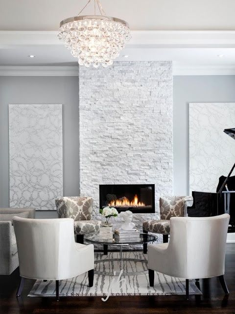 a glam neutral space with a white stone clad fireplace for a chic refined look