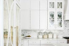 07 a gorgeous white kitchen with brass details and mirror and glass doors looks really luxurious
