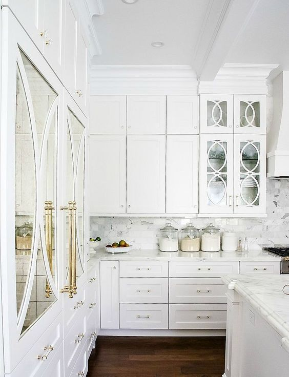 a gorgeous white kitchen with brass details and mirror and glass doors looks really luxurious