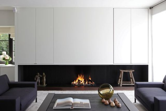 a minimalist living room with a built in fireplace under the cabinets