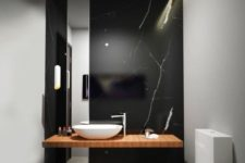 07 a refined black marble wall with white veins as a statement feature in a minimalist bathroom