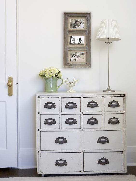 a vintage cabinet painted white with refined handles as a chic entryway console