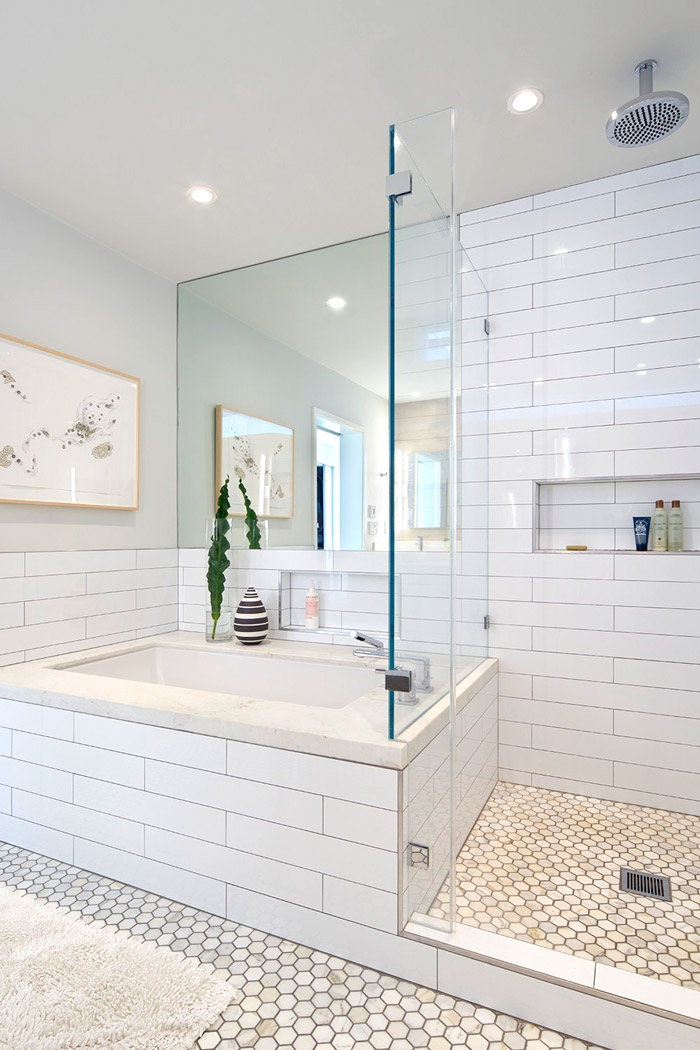 The bathroom is neutral, with subway and hexagon tiles, with a large mirror and it's light and relaxing