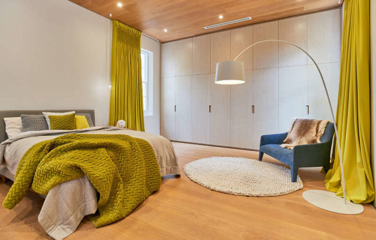 The master bedroom is done with bold pistachio touches, white cabinetry and an comfy upholstered bed