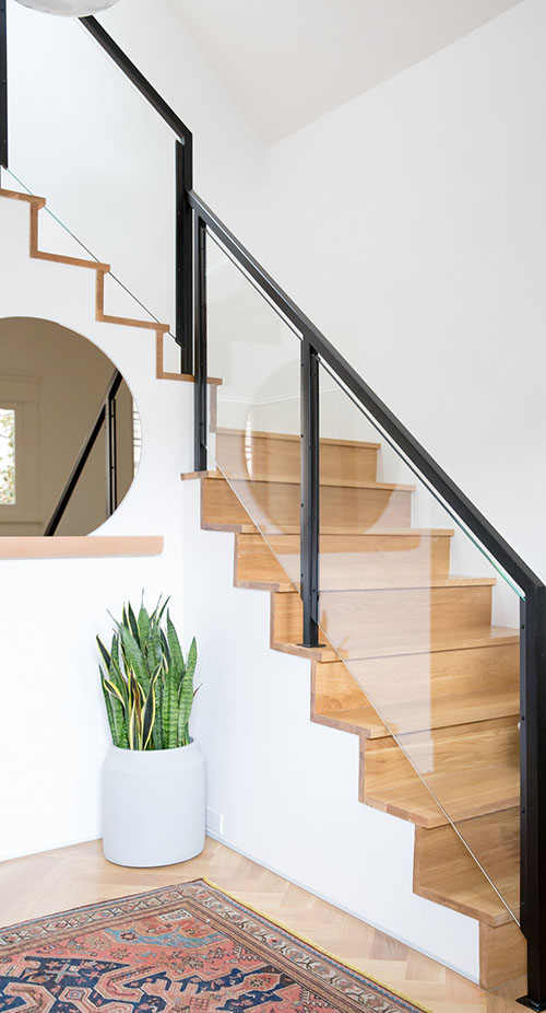 The staircase is also modern, with a black frame and glass banister that makes it super chic