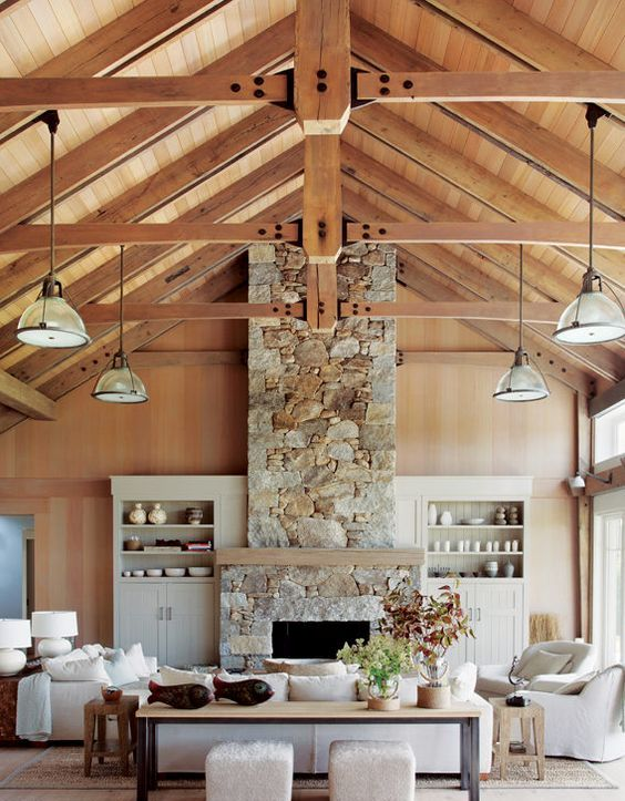 a gorgeous vacation home with a stone clad fireplace and a wooden mantel for a cozy feel
