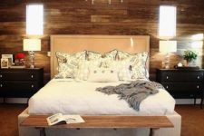 08 a gorgeous wooden wall, an animal skin rug and an upholstered bed add textures to the space