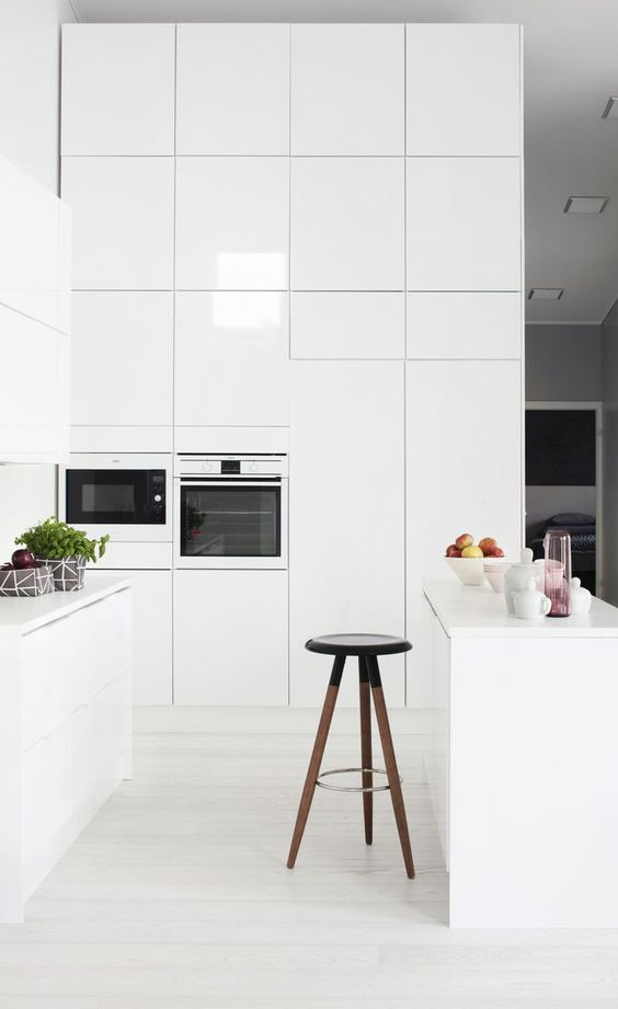 a minimalist white kitchen with no handles, a stool and tall cabinets to accomodate everything