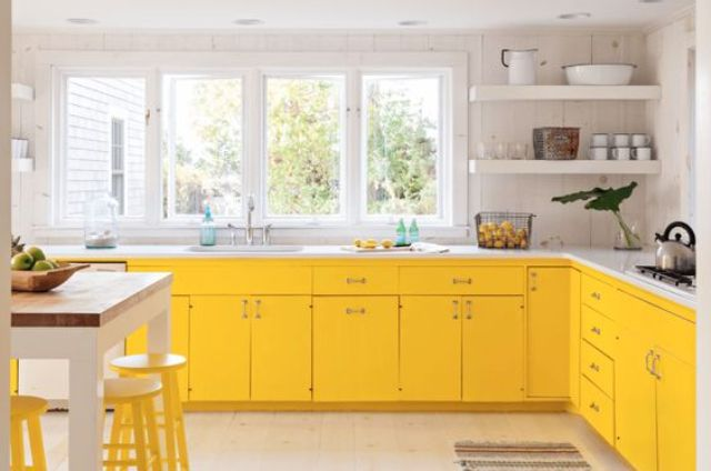 a modern farmhouse kitchen in bold yellow, with white marble counters and yellow stools looks airy and sunny