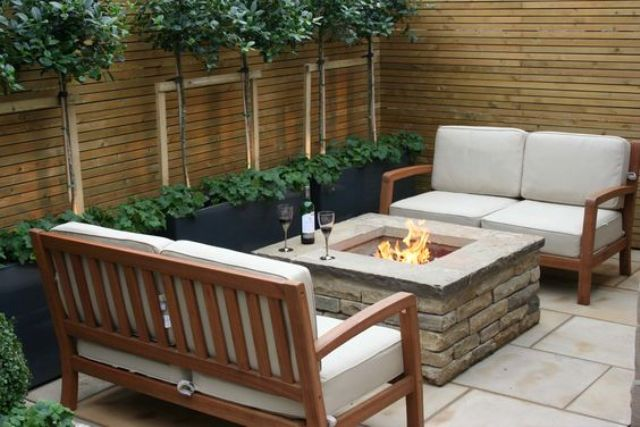 a modern outdoor space with a firepit and a couple of love seats for a romantic dinner
