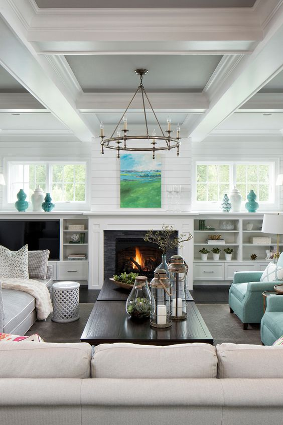 a neutral farmhouse space with a built in fireplace and some aqua colored touches