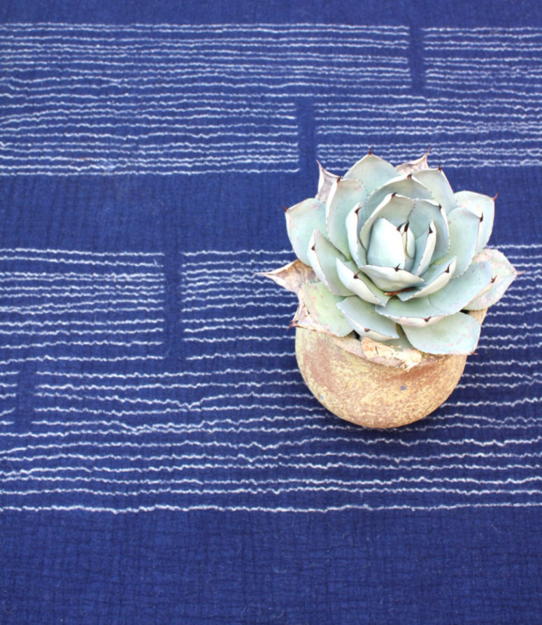 climb is a bold electric blue rug with white embroidery for chic modern rooms