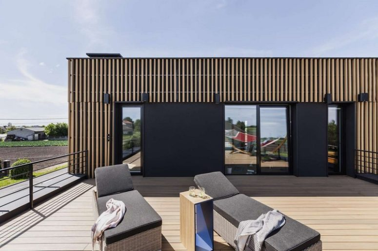 A comfy modern terrace includes two wicker loungers with upholstery