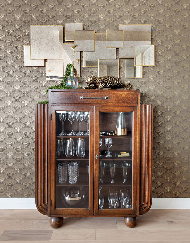 A cool wooden and glass bar cabinet with a geo mirror over it added to the interior