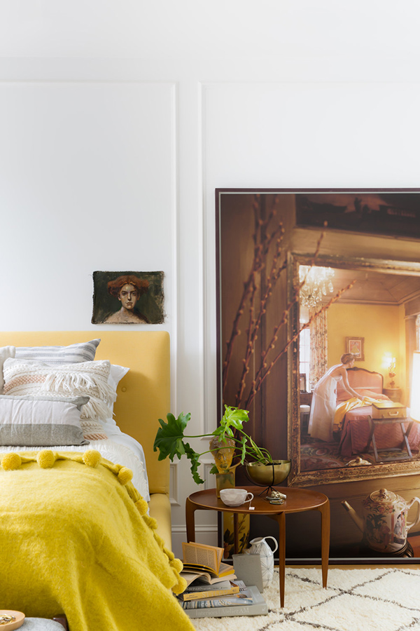 The master bedroom raises the mood with cool artworks and a sunny yellow upholstered bed