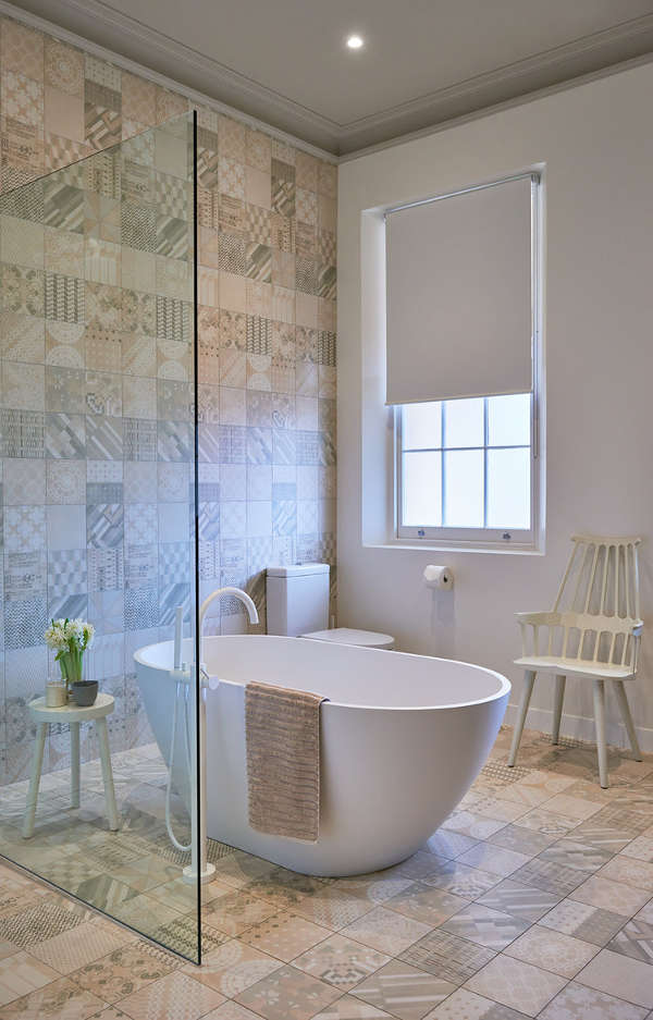 The second bathroom is done with calm-shaded mosaic tiles, a free-standing bathtub and a shower