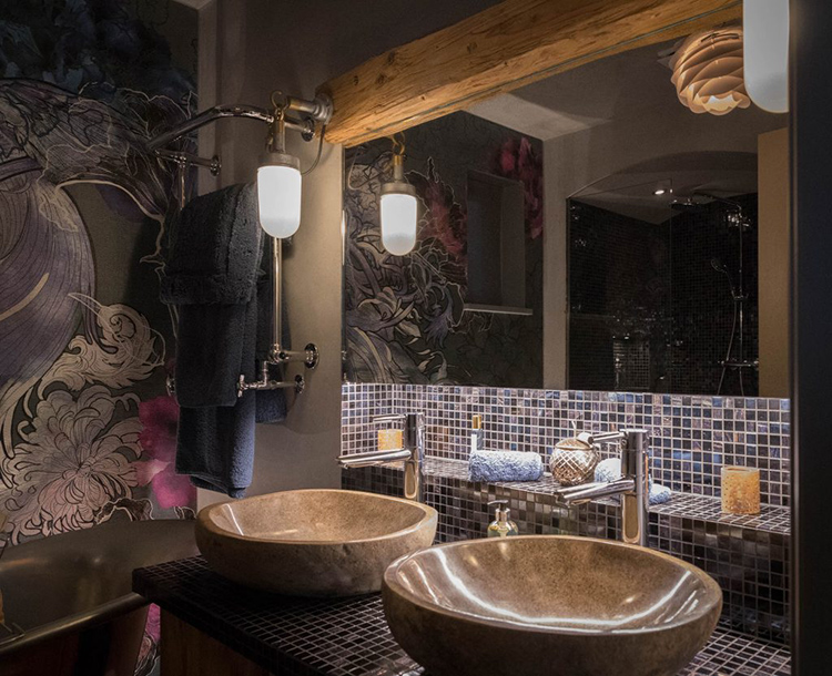 The vanity is clad with tiles and there are stone sinks