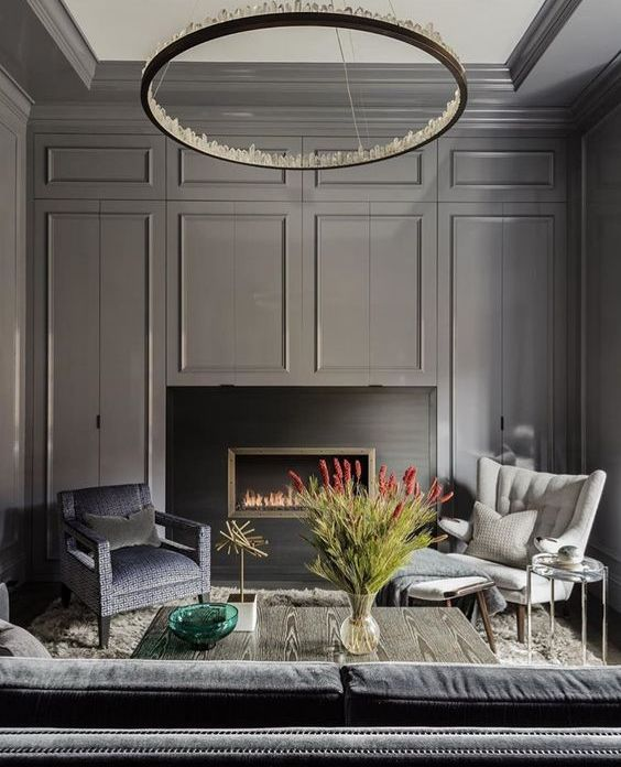 a chic moody space with graphite grey walls and a built in fireplace, a crystal chandelier is a gorgeous statement piece