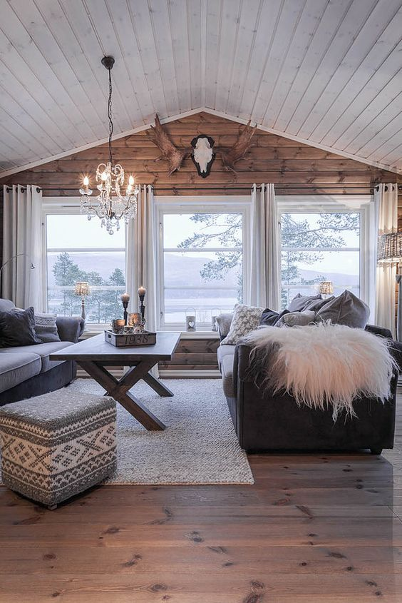 a cozy cabin-style living room with a wooden wall and several windows that bring views in