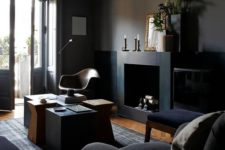09 a gorgeous elegant dark space with black walls, furniture, a fireplace and a cluster of coffee tables