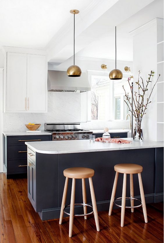 a graphite grey and white kitchen is made more glam with brass lamps and handles