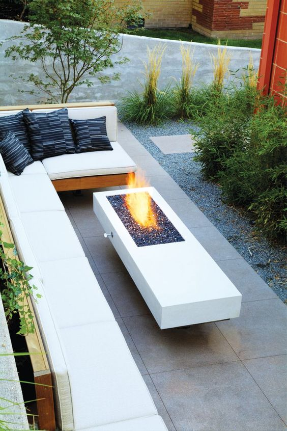 a minimalist space with an L-shaped bench and a minimal firepit looks super chic