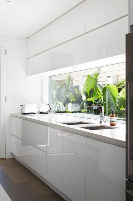 a minimalist white kitchen with a unique window backsplash which brings much light and views in