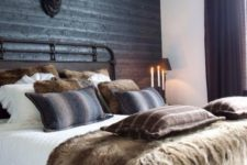 09 a rustic space with a black headboard wall of wood, a faux deer head and lots of faux fur
