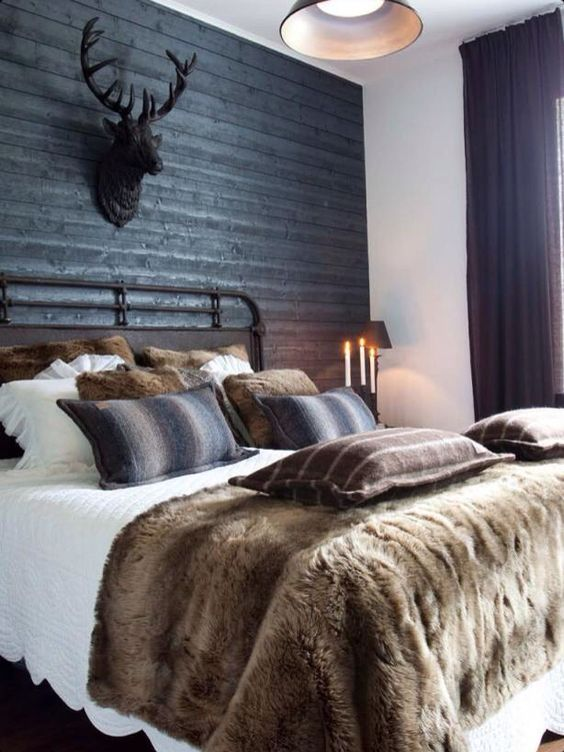 a rustic space with a black headboard wall of wood, a faux deer head and lots of faux fur
