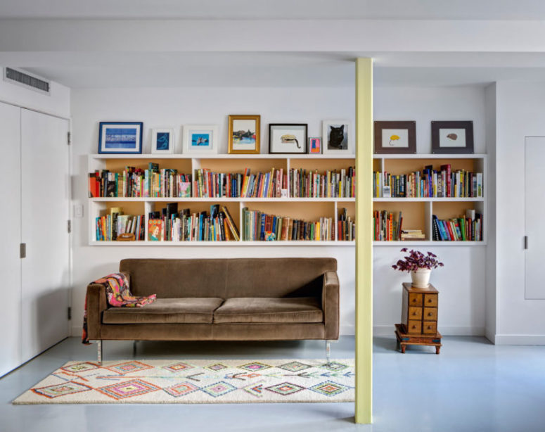 A reading nook is a must for a booklovers' home, there's a velvet sofa and many books