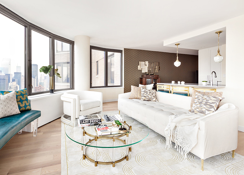 The large rounded room done in neutral shades is spruced up with a teal leather bench, glass, brass and acrylic touches
