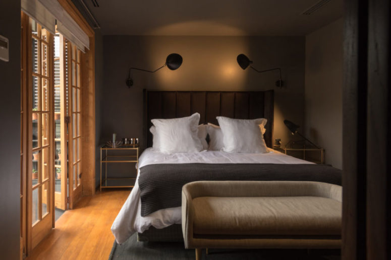 This is a master bedroom with an upholstered bed, a comfy bench, gilded touches and wall lamps