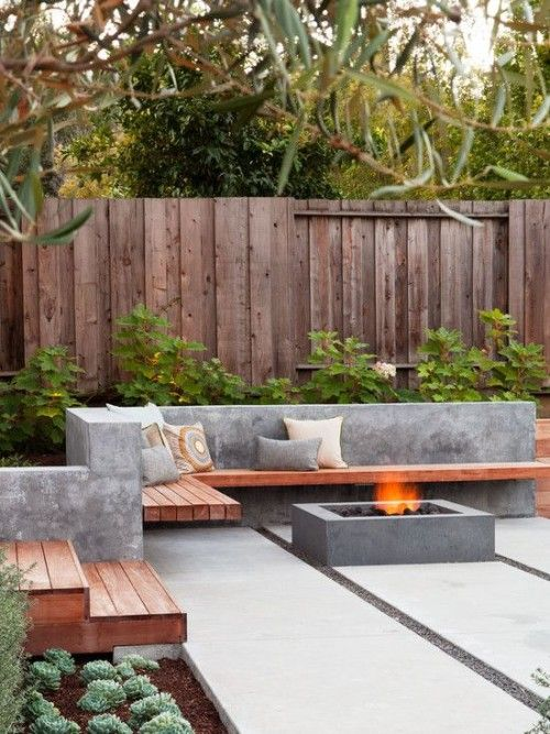 a concrete and wood L-shaped bench and a fire pit in a mmodern backyard