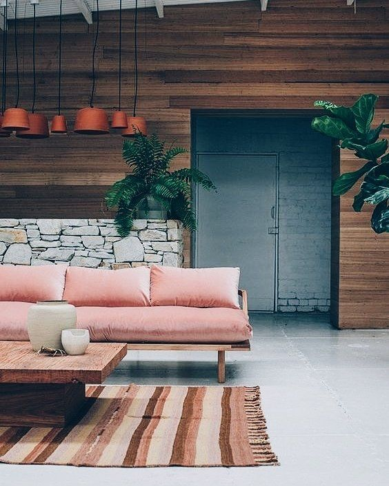 a cozy relaxed space with Asian-inspired furniture and a reclaimed wooden wall for a textural look