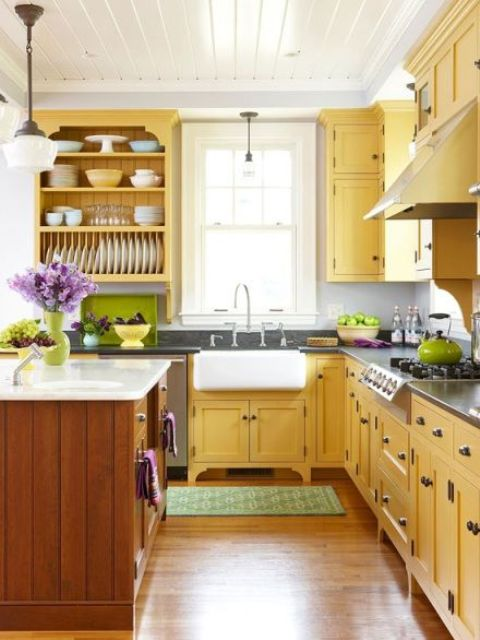 a farmhouse kitchen done in sunny yellow and natural warm-colored wood, with dark countertops and open shelving