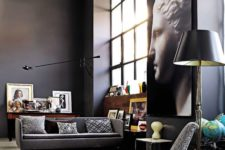 10 a gorgeous modern space with black walls, lots of artworks, big windows of double height and grey upholstery