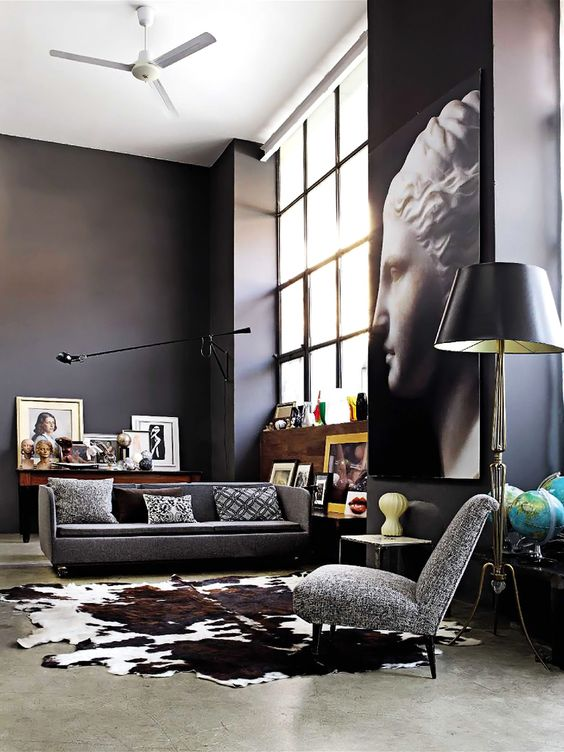 a gorgeous modern space with black walls, lots of artworks, big windows of double height and grey upholstery