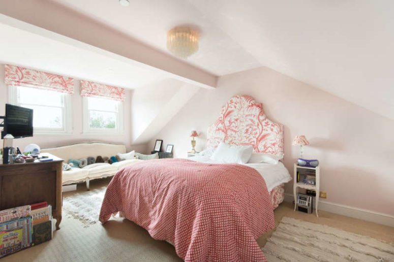 This is a guest bedroom done with the shades of pink and floral prints, the bed is upholstered and the Roman shades are matching ones