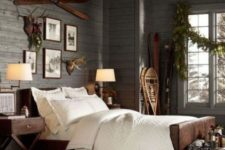 11 a chalet bedroom with a grey wooden wall, anlers and skis for a cozy feel