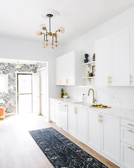 a mid-century modern kitchen done in white, with brass handles and faucets
