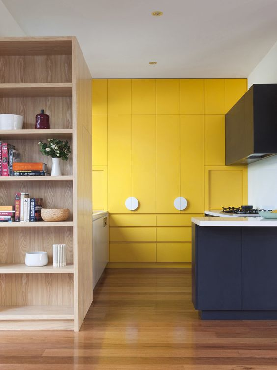 a minimalist bold yellow kitchen, with a navy and white kitchen island for a contrasting touch